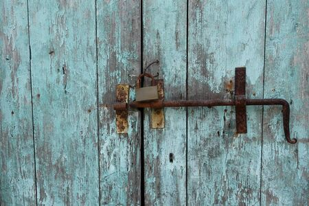 Rusty door bolt sliding latch and padlock on old weathered wooden gate with chipped blue paint.