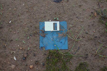 Broken floppy disk on muddy ground. Vintage computer data storage medium. Standard-Bild
