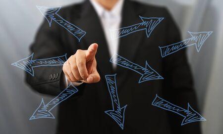 ビジネスの男性が多くの矢印をタッチします。 写真素材