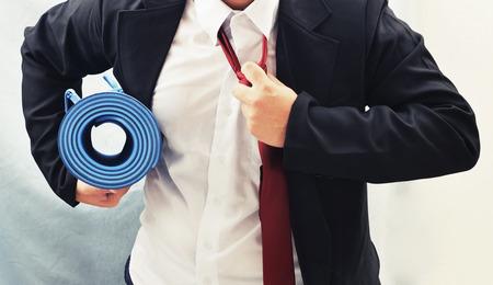ejercicio aer�bico: hombre de negocios la celebraci�n estera de yoga, el concepto de ejercicio Foto de archivo