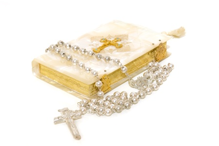 Rosary and First Communion book isolated on white background