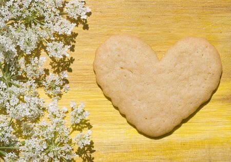 Heart-shaped biscuit on wooden background and flowers country photo