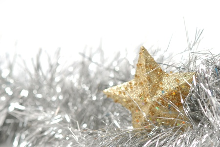 gold star and silver Christmas tinsel on a white background