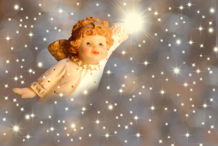 Christmas Card Angel with a light hand on starry background photo
