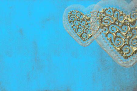 turquoise blue background with two gold hearts, with copy space photo