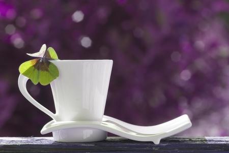 quarterfoil: cup of tea with four-leaf clover