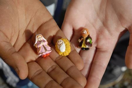 sacra famiglia: mani di due bambini con figurine di Natale Archivio Fotografico