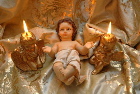 Christmas card, baby Jesus and two lighted candles on a cloth of gold Stock Photo - 11688474