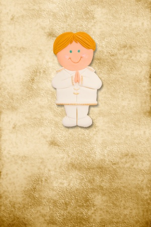 vertical card first communion, funny blond boy in parchment background photo