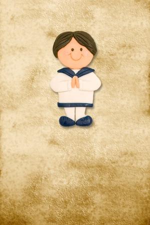 primera comunion: tarjeta vertical de la primera comunión vestido de marinero, gracioso niño en el fondo de pergamino Foto de archivo