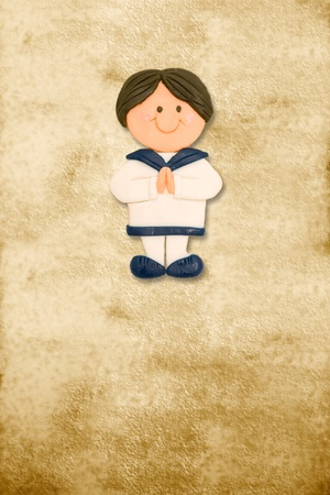 first communion: vertical card first communion dress funny toddler sailor on parchment background Stock Photo