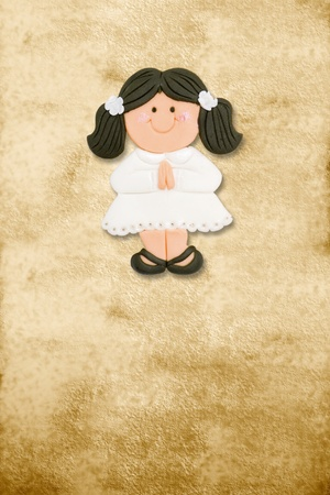 vertical card first communion, funny brunette girl in parchment background photo