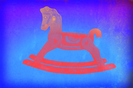 Child colorful background, red rocking horse on blue paper photo