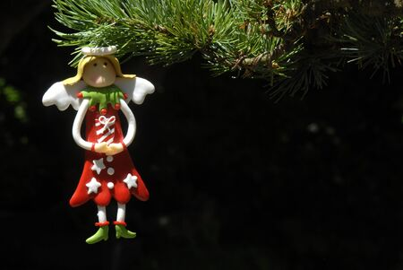 Angel hanging from Christmas tree, copy space photo