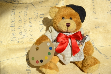 teddy bear sitting with palette and brushes photo
