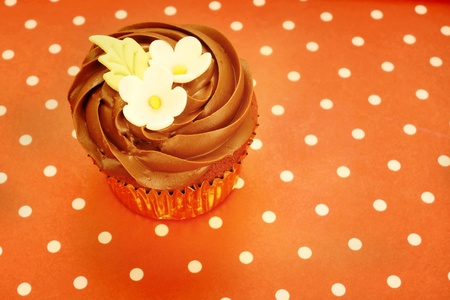 gumpaste: chocolate cupcake decorated with flowers in brown polka dot background Stock Photo
