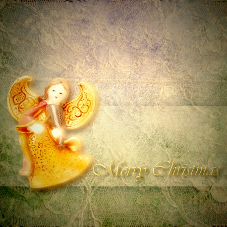 Angel musician on lace background with merry christmas text in gold letters photo