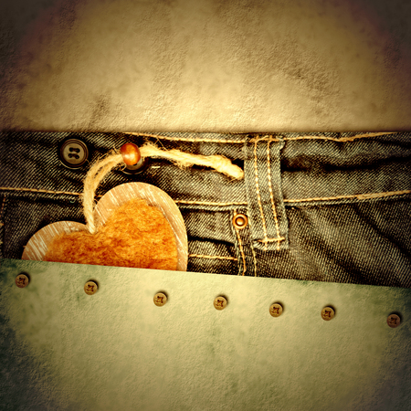grunge background young lovers, heart in jeans pocket on paper background with empty space for text photo