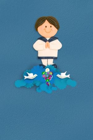 primera comunion: muchacho alegre primera comunión vestido de traje de marinero sobre fondo azul con el espacio vacío para el texto