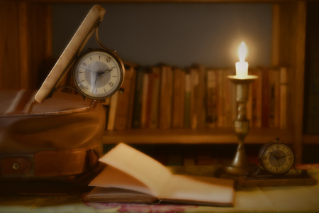 ree time to travel and read, watch old book and suitcase illuminated by candlelight photo
