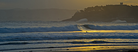 surfers catching waves at sunrise on the beach in santander with the silhouette of the Palacio de La Magdalena photo
