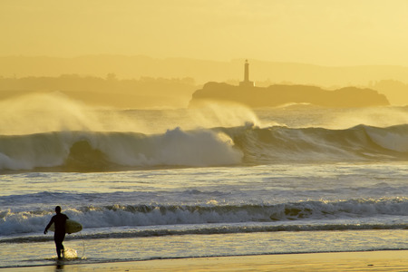 Surfer walking towards the sea at sunrise on the beach in Santander Spain, Mouro Island  photo