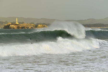 santander: Surfers on the beach in Santander, big waves with lighthouse Mouro Island