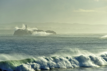 santander: Lighthouse and waves on the Island Mouro in Santander Spain