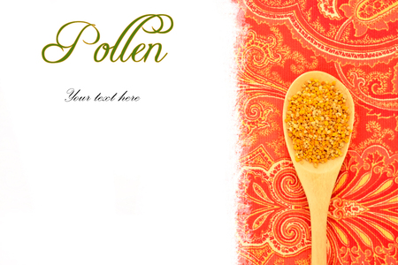 Bee pollen in wooden spoon, rustic fabric background with blank space for text photo