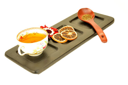 cup of herbal tea and fruit on wooden tray isolated on white background photo
