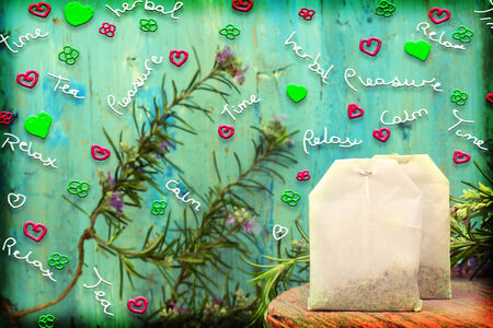 cheerful and colorful background, teabags and rosemary with flowers and cheerful text photo