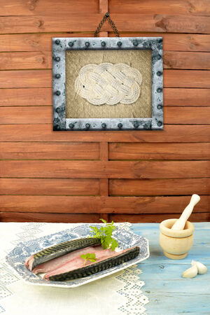 still life old  tray with  fish cooking ingredients and sailor knot picture on the wall photo