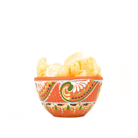 andalusian cuisine: Torreznos also called chicharrones,spanish pork rind snack, in bowl, freshly fried pork rind isolated on white background