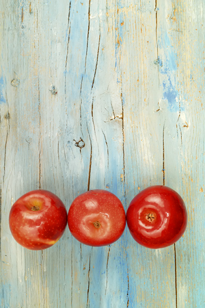 alimentation: Old wooden board with three red apples and blank space for text