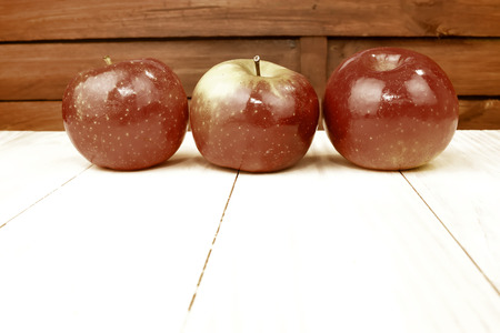 three red apples on wooden table background photo