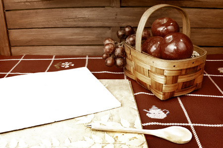 Blank recipe note book with wooden pen spoon on tabletop and fruit basket country style photo