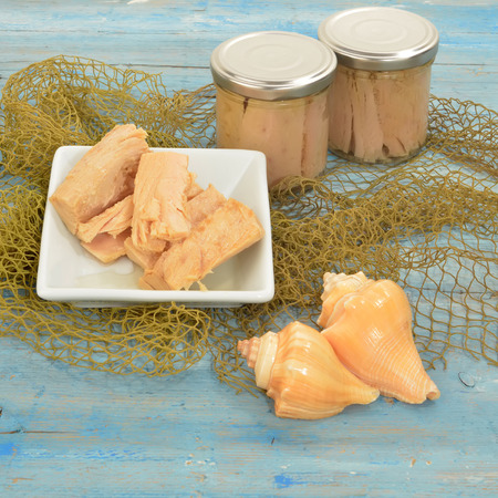 tunafish: Albacore tuna in olive oil canned glass on wooden table