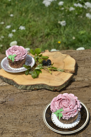 Tasty muffins with blackberries on wooden table photo