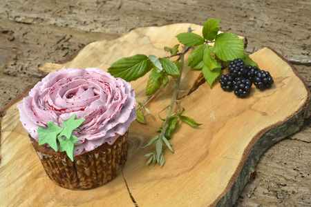 Muffin made with organic products with blackberries on old wooden table photo