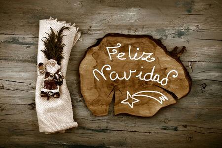 spanish language: Greeting Christmas in spanish language Feliz Navidad Merry Christmas and Santa on rustic wooden background