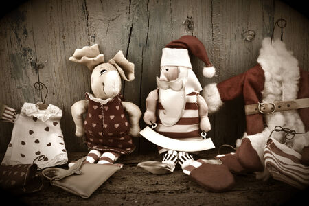 Santa Claus and Rudolf, old rag dolls on wooden background for Christmas Cards photo