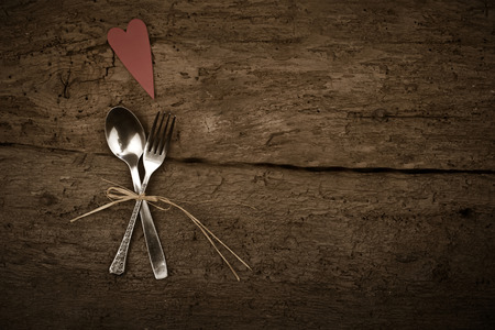 Christmas or Valentines day dinner with table setting in rustic wood style with cutlery