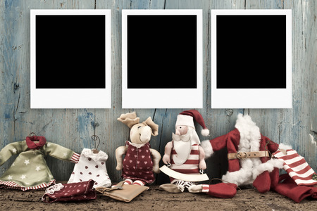 photo album cover: Christmas with three frames for photos with Santa Claus dolls on a wooden background