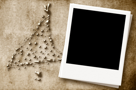 Christmas Card with empty instant photo frame on a background of parchment with a Christmas tree photo