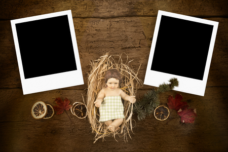 Child Jesus on a old wooden table with two phoyo frame.Christmas greeting card photo