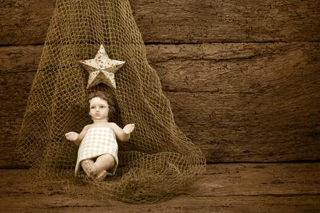 Enfant Jésus de Noël sur un filet de pêche sur le vieux fond en bois avec un espace vierge pour écrire ou la photo