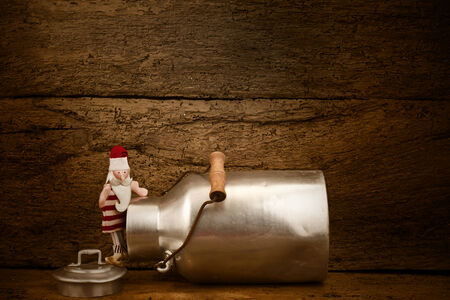 Funny Christmas card, old milk can and Santa Claus on a old wooden background with space for writing or put photo photo
