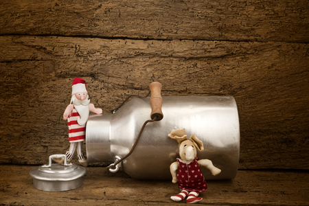 Funny Christmas card, vintage milk can Santa Claus and  reindeer  on a old wooden background with space for writing photo