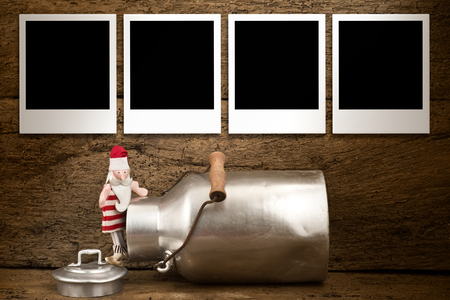 Christmas photos frames card, Funny Santa and milk can  with four empty instant  photos  frames hanging on old wooden wall photo
