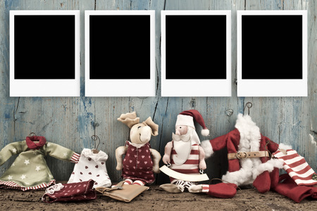 Christmas four empty photo frames and vintage Santa dolls on wooden background